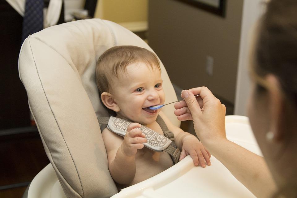 Dítě krmení v jídelní židličce