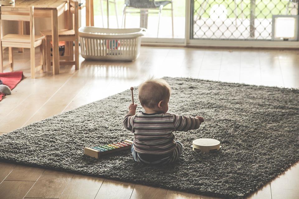 Dítě si hraje na koberci