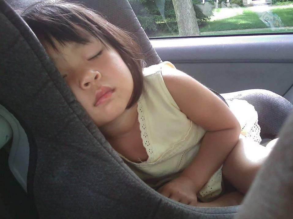 Dítě spící v dětské autosedačce